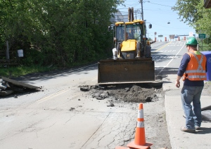 Exclusive! For real! Honest! Quebec road workers repair the sink hole at the border between Stanstead, Quebec and Derby Line, Vermont.
